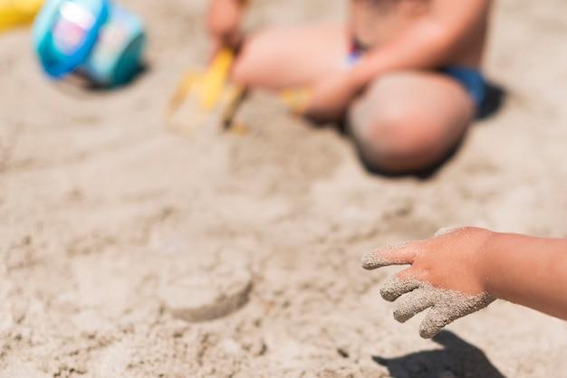 Schließen sie oben von den kinderhänden, die mit sand am strand spielen
