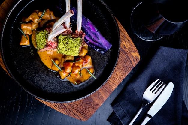 Schließen sie oben von den lammkoteletts mit gemüse mit einer soße des karamells, des pfeffers und der gewürze in einer restauranteinstellung.