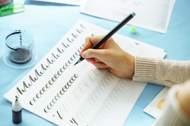 Schließen sie oben von den mädchenhänden, die lernen, briefe auf papier zu schreiben
