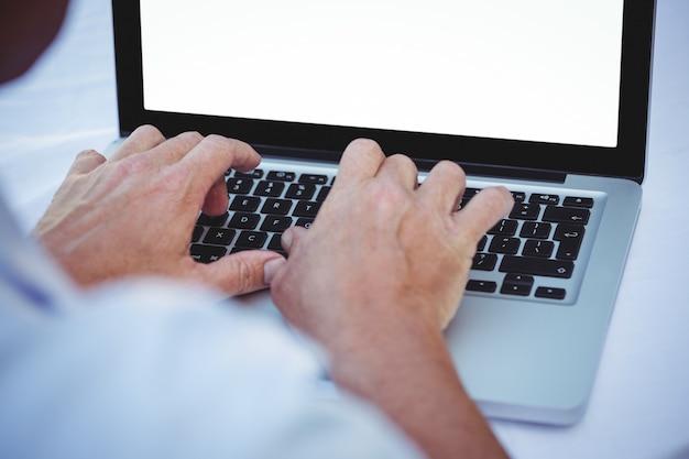 Schließen sie oben von den männlichen händen, die auf laptop schreiben