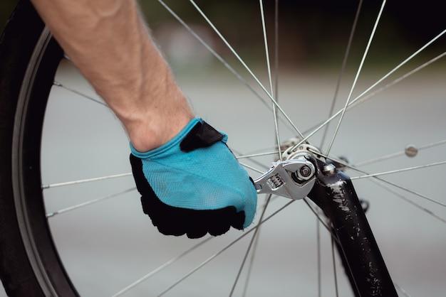 Schließen sie oben von den männlichen händen in den sporthandschuhen, die mountainbike fixieren, pannen während des fahrens im park