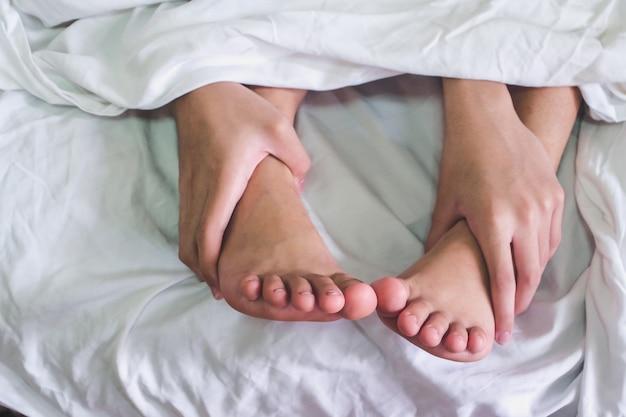 Schließen sie oben von den männlichen und weiblichen füßen auf einem bett und von paaren, die sex im schlafzimmer haben.