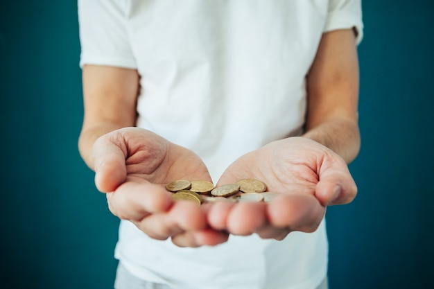 Schließen sie oben von den mannhänden, die euro-geldmünzen halten und zählen.