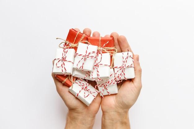 Schließen sie oben von den mannhänden, die rot und weiß verpackte geschenkboxen mit band auf weiß halten