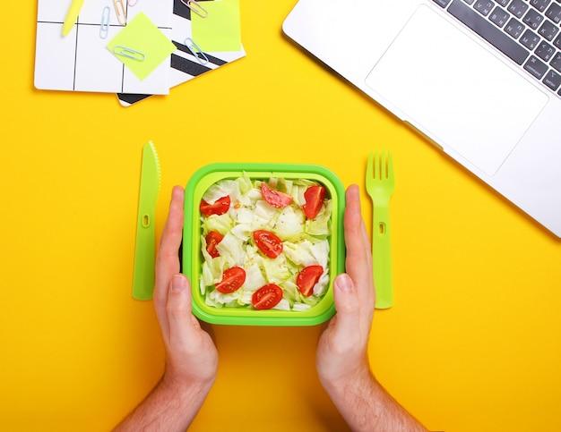 Schließen sie oben von den mannhänden mit dem essen im plastikbehälter. mann, der frischen salat während der arbeit isst. gesundes nahrungsmittelkonzept. draufsicht, flache lage, gelber hintergrund. gesunder snack am büroarbeitsplatz.