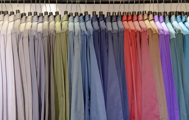 Schließen sie oben von den multi farbigen hemden auf aufhängern, bunter kleiderstoffhintergrund