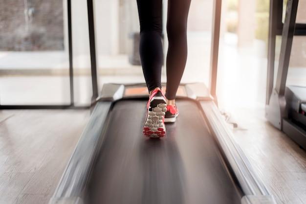 Schließen sie oben von den muskulösen beinen der frau, die auf tretmühlentraining an der eignungsturnhalle laufen