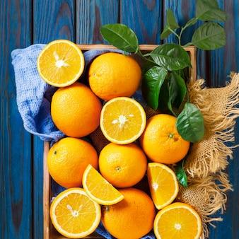 Schließen sie oben von den orangen auf einem blauen küchentuch mit grünen blättern. stillleben