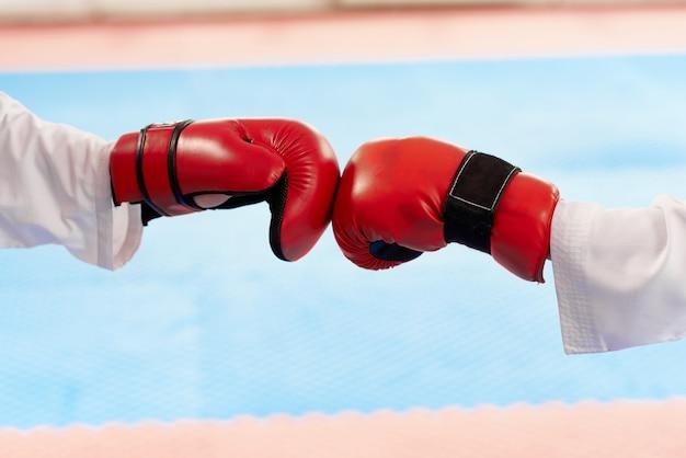 Schließen sie oben von den roten boxhandschuhen, die zusammen an der hellen klasse schlagen.