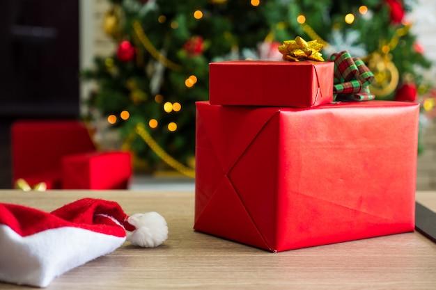 Schließen sie oben von den roten geschenkboxen auf holztisch mit verziertem weihnachtsbaumhintergrund.