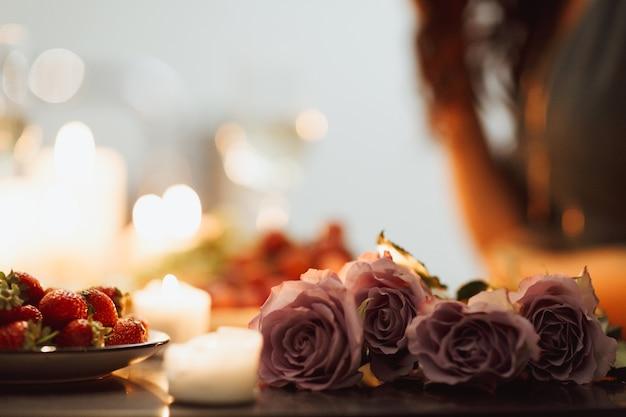 Schließen sie oben von den schönen violetten rosen, die auf tisch mit kerzen und erdbeeren liegen