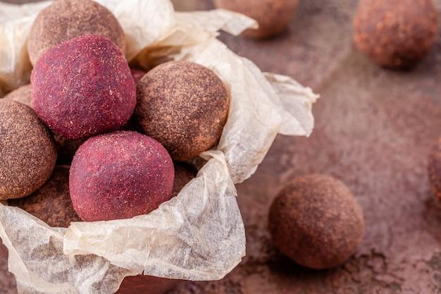 Schließen sie oben von den selbst gemachten rohen kakaobällen des strengen vegetariers in der schüssel mit kraftpapier