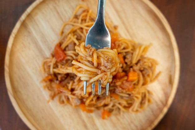 Schließen sie oben von den spaghettis auf hölzernem teller
