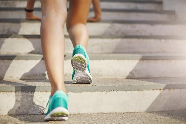 Schließen sie oben von den sportlichen beinen der jungen frau, die sich vorbereiten, auf ihrem täglichen städtischen training nach oben zu laufen. gesundes lebensstilkonzept.