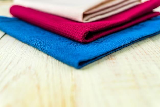 Schließen sie oben von den stoffservietten von beige, blauen und burgunder-farben auf rustikalem weißem holztisch. geringe schärfentiefe.