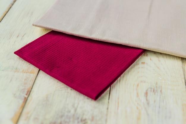 Schließen sie oben von den stoffservietten von beige- und burgunder-farben auf rustikalem weißem holztisch.