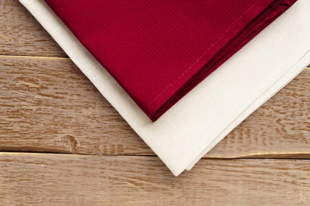Schließen sie oben von den stoffservietten von beige und von burgunder-farben auf rustikalem braunem holztisch.