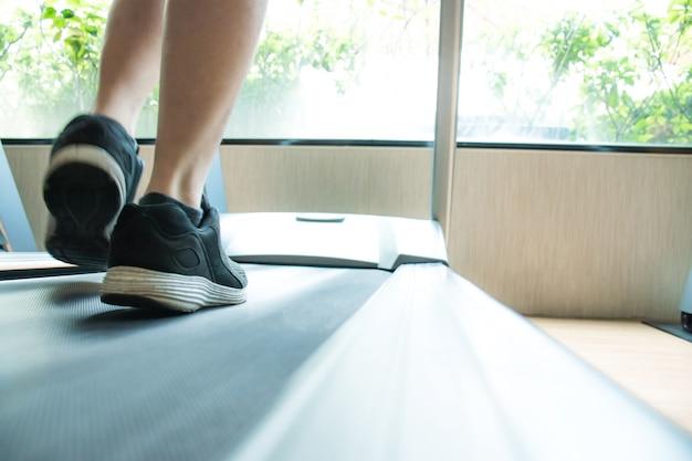 Schließen sie oben von den turnschuhen der jungen männer, die auf dem laufband im fitnessstudio laufen