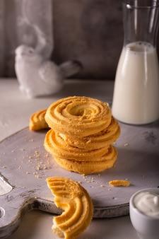 Schließen sie oben von den vanillekeksen und der tasse milch auf einem weißen holzbrett