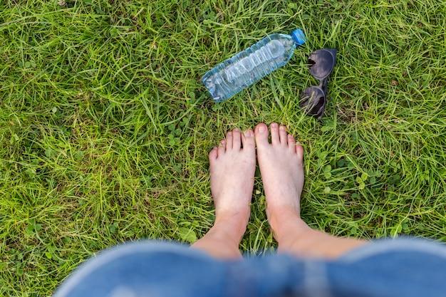 Schließen sie oben von den weiblichen beinen auf dem gras in einem park an einem sonnigen tag. plastikflasche mit klarem wasser und sonnenbrille im grünen gras. präsentieren sie ihr produkt