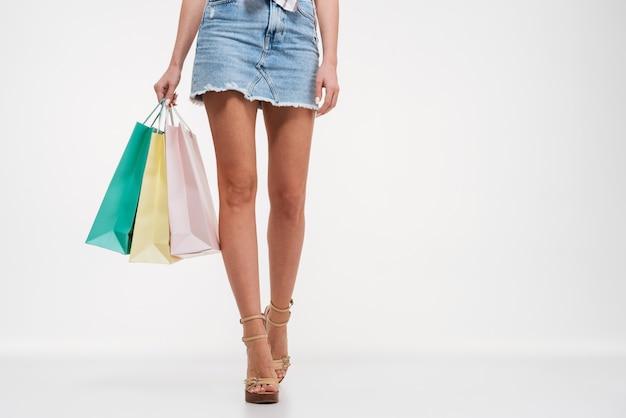 Schließen sie oben von den weiblichen beinen im rock, der einkaufstaschen hält