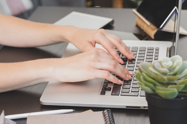 Schließen sie oben von den weiblichen händen des frauenbüroangestellten, der auf der tastatur schreibt