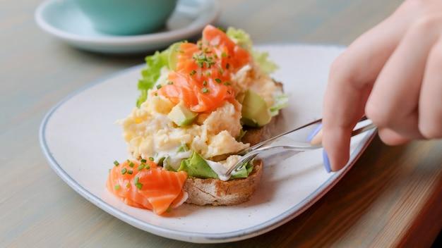 Schließen sie oben von den weiblichen händen, die avocadotoast mit lachsen und ei beim frühstücken schneiden