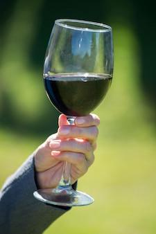 Schließen sie oben von den weiblichen händen, die ein glas wein halten