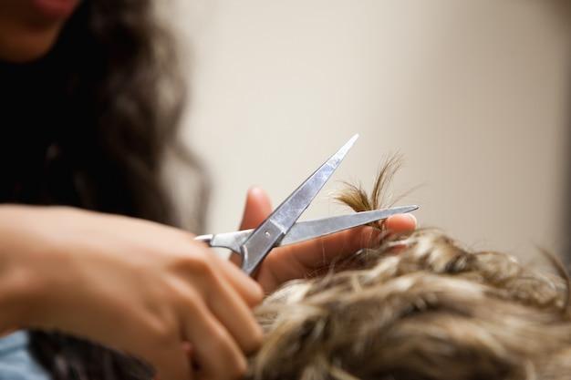 Schließen sie oben von den weiblichen händen, die haar mit scheren schneiden