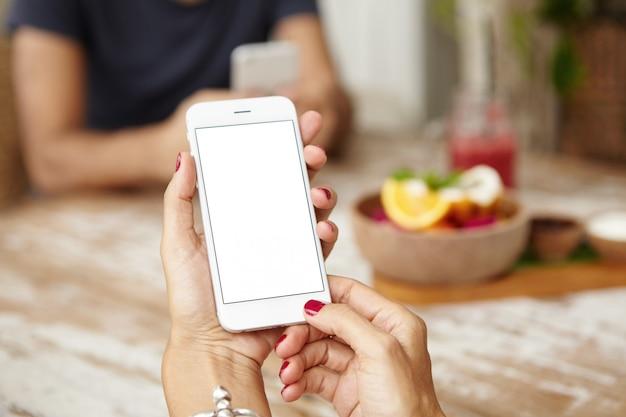 Schließen sie oben von den weiblichen händen mit den roten nägeln, die smartphone mit leerem kopierraumbildschirm für ihren text oder werbeinhalt halten. kaukasische frau, die internet auf handy während des mittagessens surft.