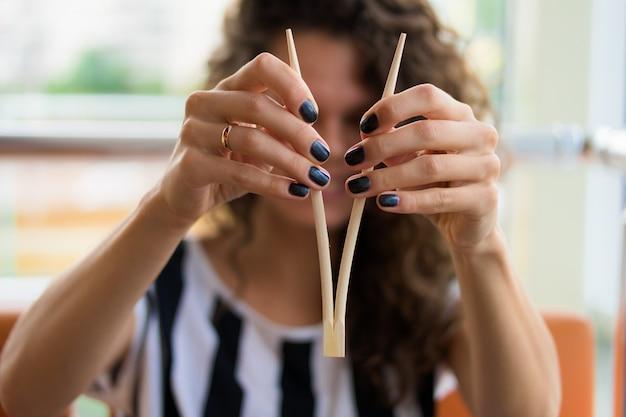 Schließen sie oben von den weiblichen händen mit der maniküre, welche die essstäbchen für sushi hält