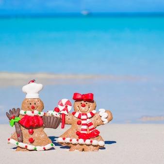 Schließen sie oben von den weihnachtslebkuchenplätzchen auf einem weißen sandigen strand