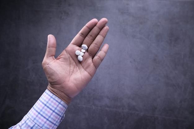 Schließen sie oben von den weißen pillen auf der handfläche