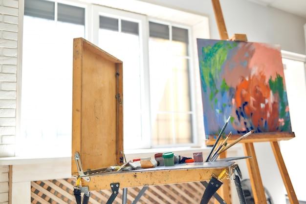 Schließen sie oben von den zeichnungsinstrumenten und -werkzeugen, von den künstleraquarellbürsten und von der gestell mit abstraktem bild