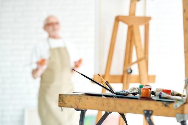 Schließen sie oben von den zeichnungsinstrumenten und -werkzeugen, von den künstleraquarellbürsten und von der gestell mit männlichem künstler