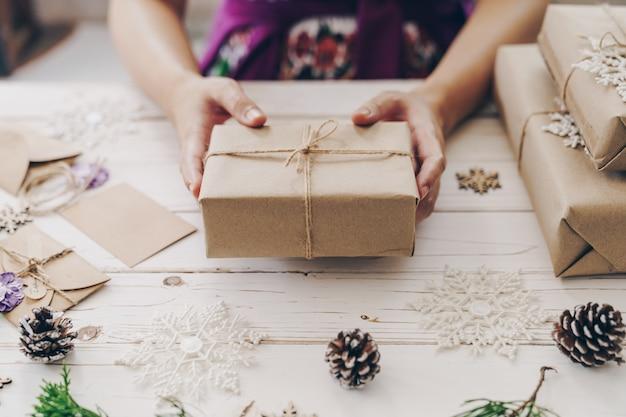 Schließen sie oben von der anwesenden geschenkbox der handfrau auf holztisch mit weihnachtsdekoration.