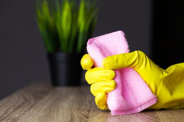Schließen sie oben von der arbeiterhand, die staub im büro in den gelben handschuhen abwischt