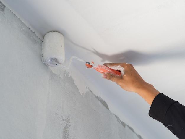 Schließen sie oben von der arbeitskrafthand, die rolle verwendet und bürsten sie für malereiwand. haus gebäudekonzept.