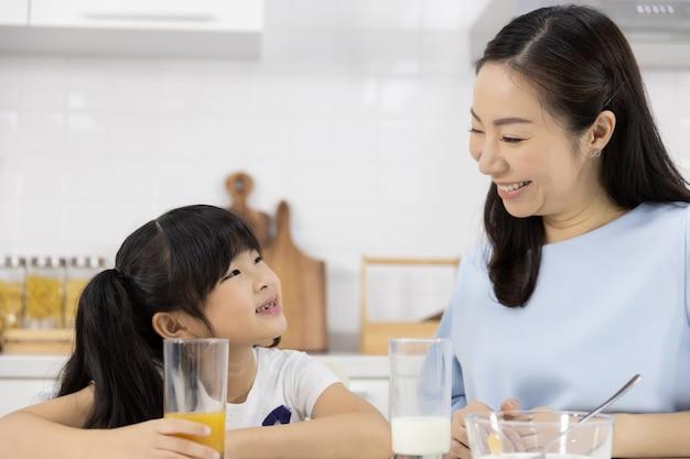 Schließen sie oben von der asiatischen familie, die orangensaft trinkt