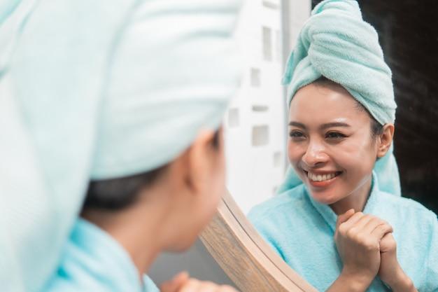 Schließen sie oben von der asiatischen frau, die auf spiegelung im spiegel nach dusche am badezimmer schaut