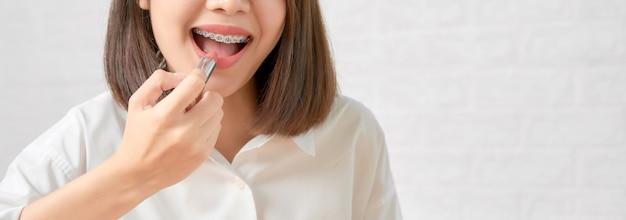 Schließen sie oben von der asiatischen frau, die herrlich charmant ist und rosa lippenstift mit berührungsmund hält.