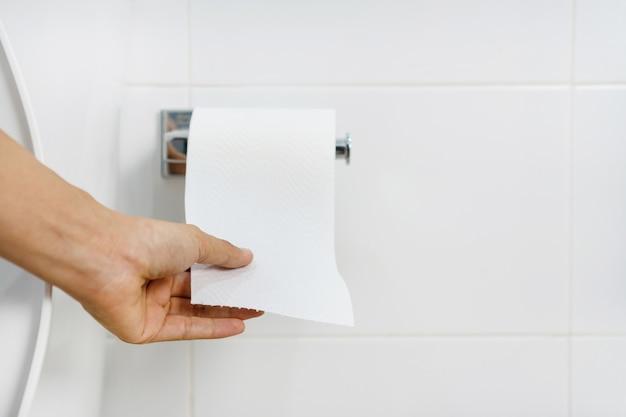 Schließen sie oben von der asiatischen frau, die papier im badezimmer zieht