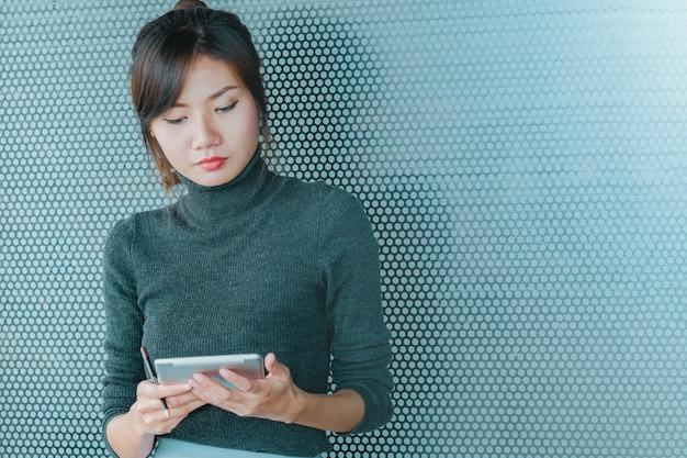 Schließen sie oben von der asiatischen geschäftsfrau, die an tablette arbeitet