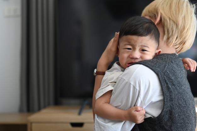Schließen sie oben von der asiatischen mutter, die weinendes baby im bequemen zuhause hält