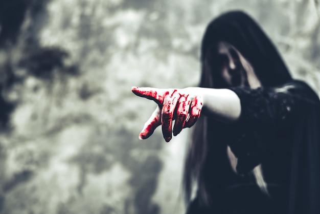 Schließen sie oben von der blutigen geisterhand, die auf die front zeigt. horror und geist konzept