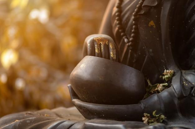 Schließen sie oben von der buddha-statue der schwarzen mönchalmosenschüssel
