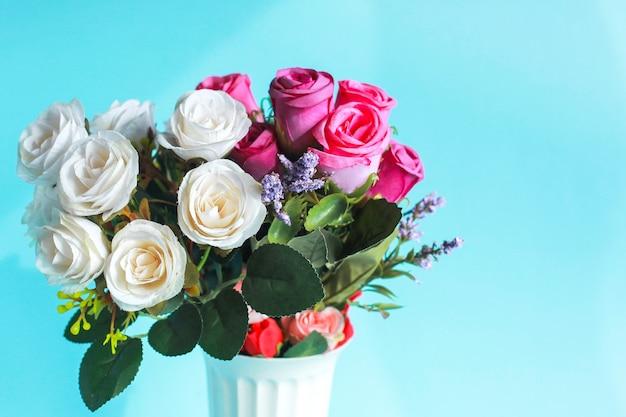 Schließen sie oben von der bunten künstlichen rosenblume lokalisiert auf blauem hintergrund