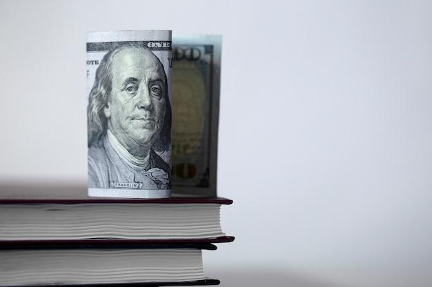 Schließen sie oben von der dollarnote mit benjamin franklin auf büchern auf einem weißen hintergrund