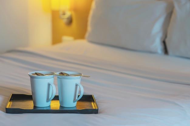 Schließen sie oben von der doppelwillkommenskaffeetasse auf weißem bett im hotelzimmer - hotelbrunnengastfreundschafts-urlaubsreisekonzept