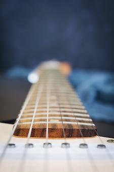 Schließen sie oben von der e-gitarre auf dunkler oberfläche